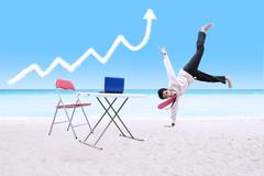 Businessman dancing under growth graph cloud and laptop - stock photo