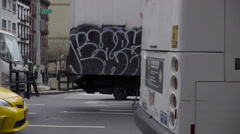 Cars and graffiti truck driving down 2nd ave, Queensboro Bridge background NYC Stock Footage