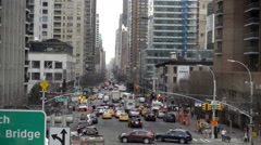 Ed Koch Queensboro Bridge sign from moving overhead tram over busy street NYC Stock Footage