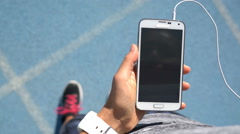 Female Runner Playing Music On Smart Phone - Sporty Healthy Lifestyle Video - stock footage