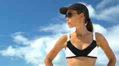Sporty Woman Standing With Hands On Hip At Beach - Girl Wearing Sunglasses - stock footage