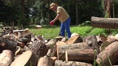 Tired man chop wood and drink water from plastic bottle. 4K Stock Footage