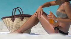 Woman Applying Sunscreen Lotion On Leg At Beach - Tanning Oil Spray Bottle - stock footage
