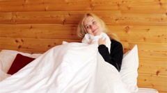Girl sitting on the bed with a blanket Stock Footage
