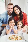 Family of four enjoying pizza while sitting on sofa Stock Photos
