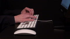 Hands typing on keyboard and using the mouse to surf the internet - stock footage