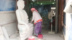 Woman works with Buddha marble statue in Tampawaddy Quarter of Mandalay Stock Footage