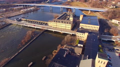 Flyover of springtime riverfront with buildings, damn, bridge, raging waters Stock Footage