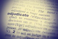 Dictionary definition of adjudicate. Close up view with paper textures Stock Photos