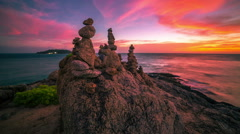 4K TimeLapse. Sunset on the background tourist pyramid of stones on cape at the Stock Footage