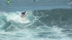 A surfer rides a wave in the surf at the ocean blue in the surf spot. - stock footage