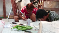 Workers etch and paint the words on marble plates in Mandalay street Stock Footage