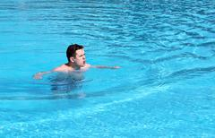 Young  emotional man swimming in the pool - stock photo