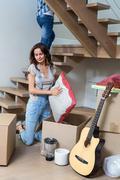 Woman unpacking cushion from cardboard box - stock photo