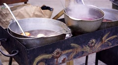 Bowls with delicious mulled wine cooking on charcoal, street vendor making food - stock footage