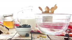 Cereal and dried fruits are poured into a breakfast bowl, slow motion Stock Footage