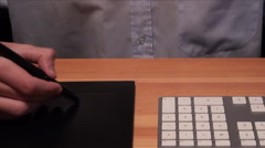 A designer drawing on a professional drawing tablet and keyboard Stock Footage