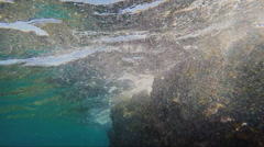Surf under water, waves breaking on the rocks Stock Footage