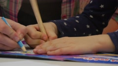 Teacher is Painting With Kid in Coloring Book With Pencils Hands Close up Kid Stock Footage