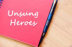 Unsung heroes write on notebook - stock photo