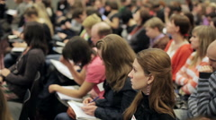 Listener at the conference in a large room listening to the speaker - stock footage