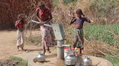 Indian rural girls pour water from the pump to the jugs.Rajasthan.Maunt-Abu.2016 - stock footage