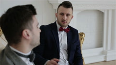 Close-up. Two businessmen in suits with bow ties are communicating Stock Footage