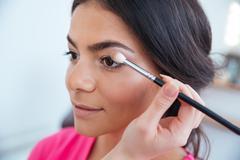 Makeup artist applying eyeshadow to attractive woman Stock Photos