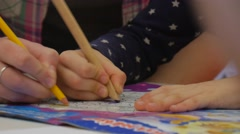 Stock Video Footage of Woman is Painting With Kid in Coloring Book Yellow Pencil Hands Close up Kid