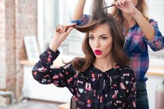 Woman hairdresser combing long hair of girl with red lipstick - stock photo