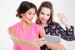 Two beautiful smiling young women making selfie using mobile phone Stock Photos