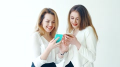 two young women with mobile phone on white background - stock footage