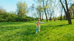 Stock Video Footage of Colorful cheerful girl running away from the camera in the park