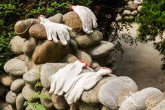 Gloves workers were left on a stone wall. - stock photo