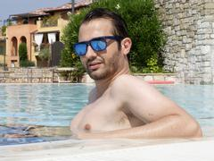 Man relaxing in a swimming pool - stock photo