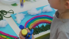 Kid is Collecting a Pencils From a Table Girl Sitting at Her Rainbow-Applique Stock Footage
