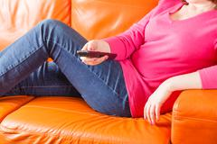 Woman sitting on sofa and swith TV channels Stock Photos