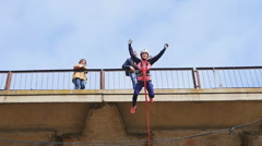 Girl jumping from the bridge down, waving his arms Stock Footage