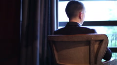 A thoughtful young man is sitting on retro armchair in front of the window. - stock footage