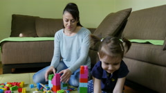 Cute female child and young  attractive mother playing with colorful dices. Stock Footage