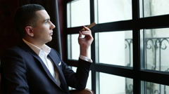 Young businessman in a classic suit sitting in front of the window with cigar Stock Footage