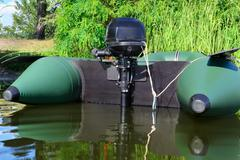Inflatable boat with motor on the river near a shore - stock photo