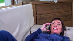 Telling some great news to a friend on the phone - stock footage