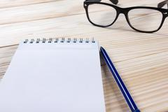 Back to school. Blank note pad, notebook with pen and glasses - stock photo