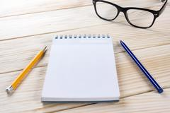 Back to school. Blank note pad, notebook with pen and glasses Stock Photos
