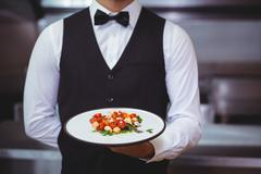 Handsome waiter holding a plate - stock photo