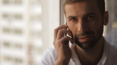 A man in a white shirt speaks on a mobile phone Stock Footage