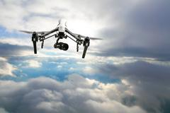 Drone for industrial works flying above clouds Stock Photos