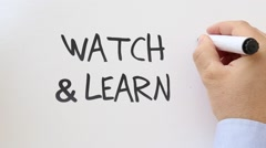 Watch and learn written on whiteboard Stock Footage