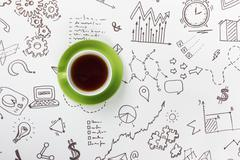 Coffee cup on background of business strategy - stock photo